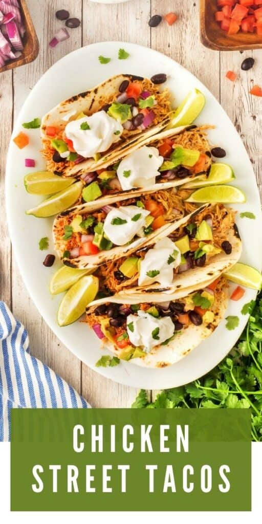 Overhead view of chicken street tacos on a large white plate loaded with toppings and recipe title on bottom of photo