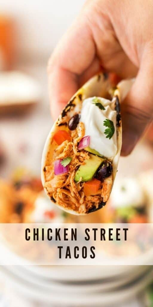 One chicken street taco being held by a hand facing the camera with recipe title on bottom of image