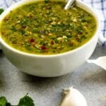Bowl of chimichurri sauce with ingredients around it with recipe title on bottom of image