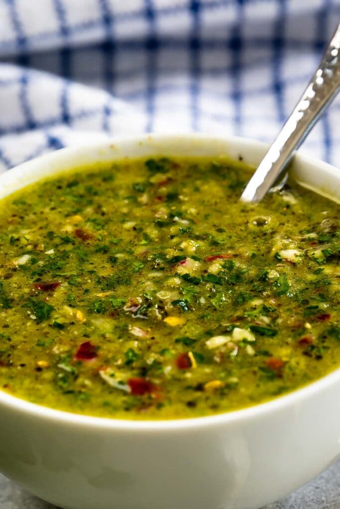 Close up shot of chimichurri sauce in a white bowl