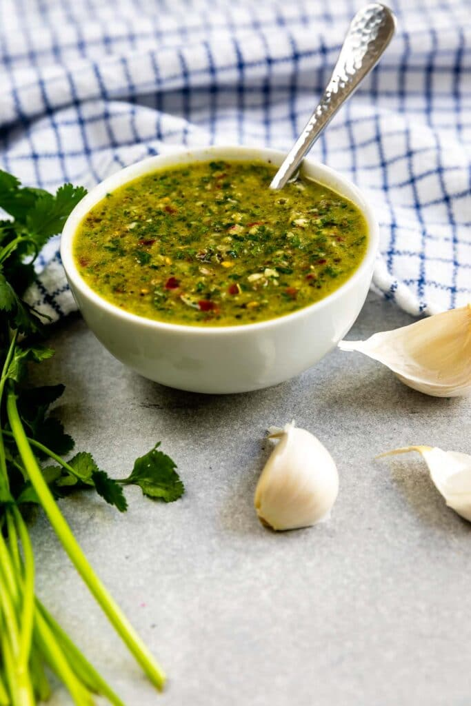 Bowl of chimichurri sauce with ingredients around it