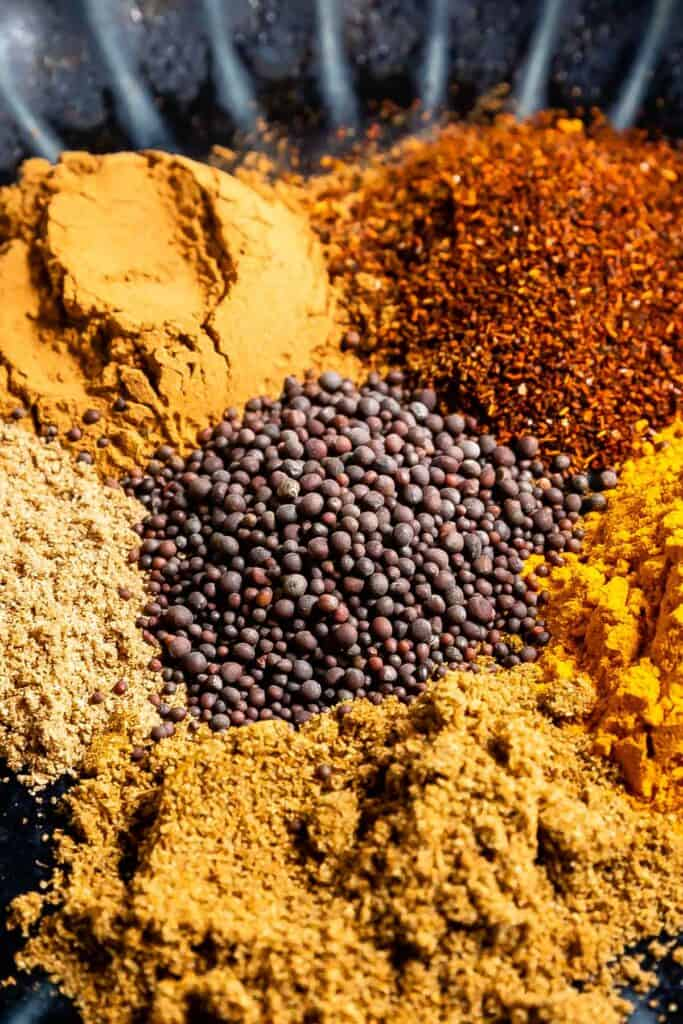 Close up shot of spices needed to make homemade curry powder