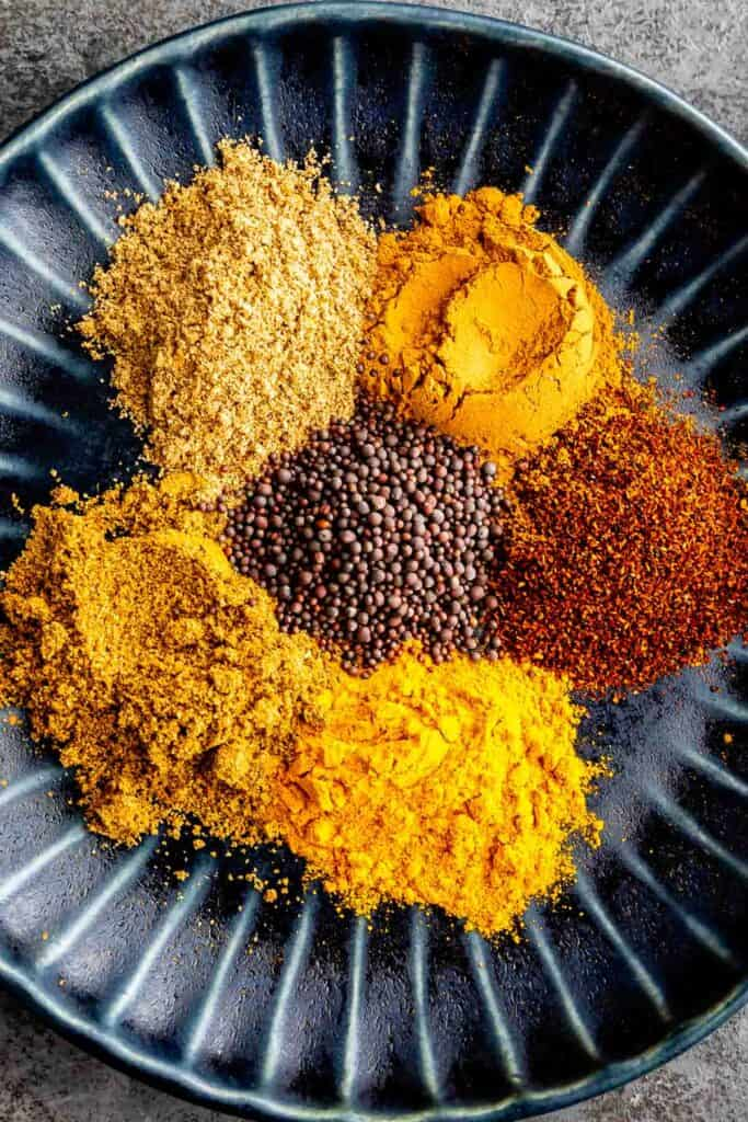 Overhead shot of all spices separated on a plate that make curry powder