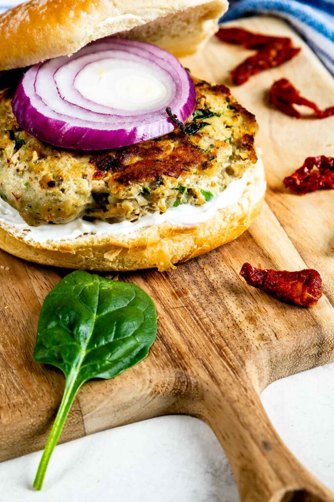 Greek turkey burger on a wooden cutting board topped with red onion