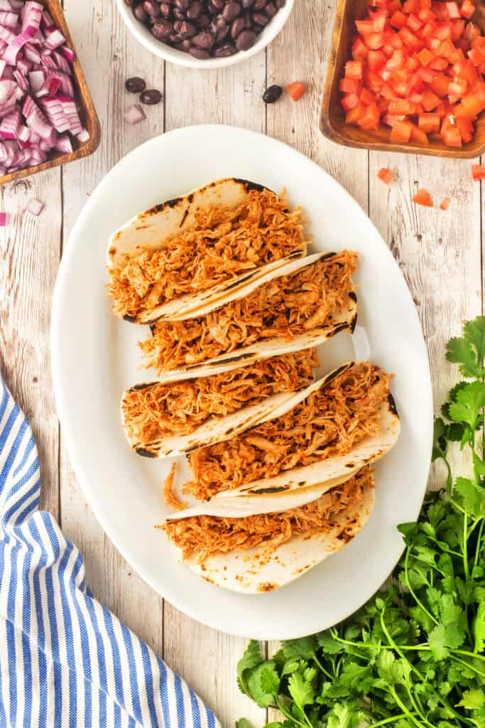 Overhead shot of chicken street tacos filled with shredded chicken