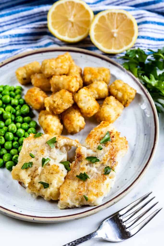 Pan seared cod on a plate served next to peas and tater tots