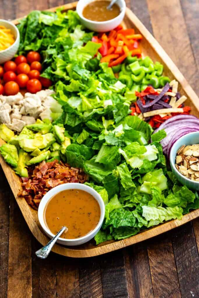 Overhead shot of salad bar board with all the ingredients and dressings