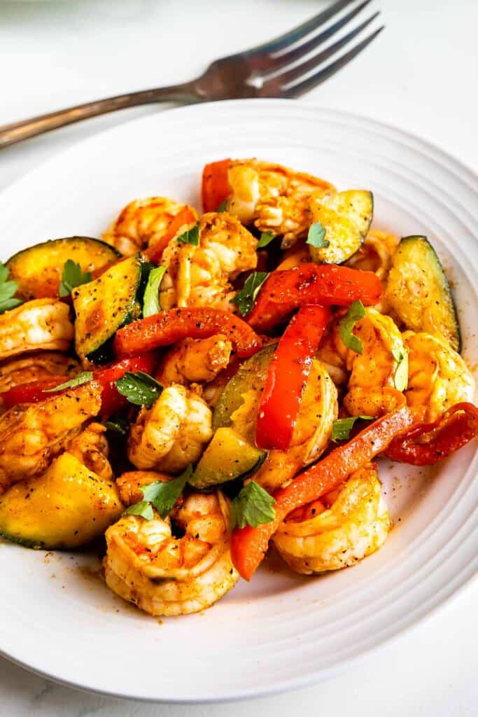 Overhead shot of shrimp and vegetable skillet served on a white plate