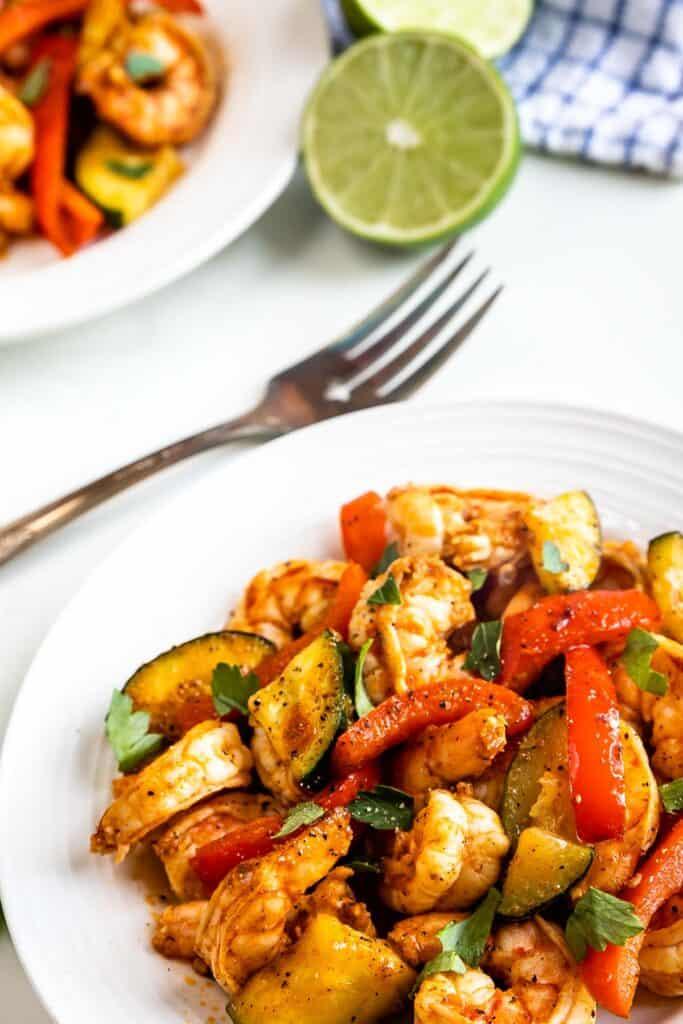 Close up shot of shrimp and vegetable skillet dinner served on a white plate