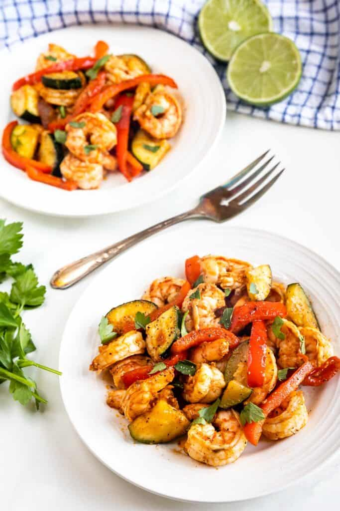 Overhead shot of two plates of shrimp and vegetables skillet dinner