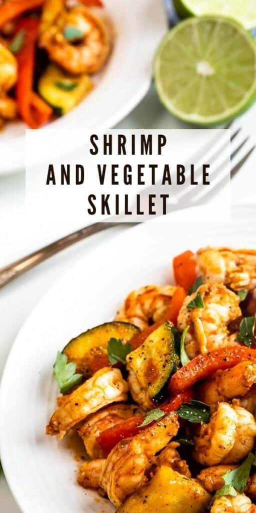 Close up shot of shrimp and vegetable skillet dinner served on a white plate with recipe title in middle of photo