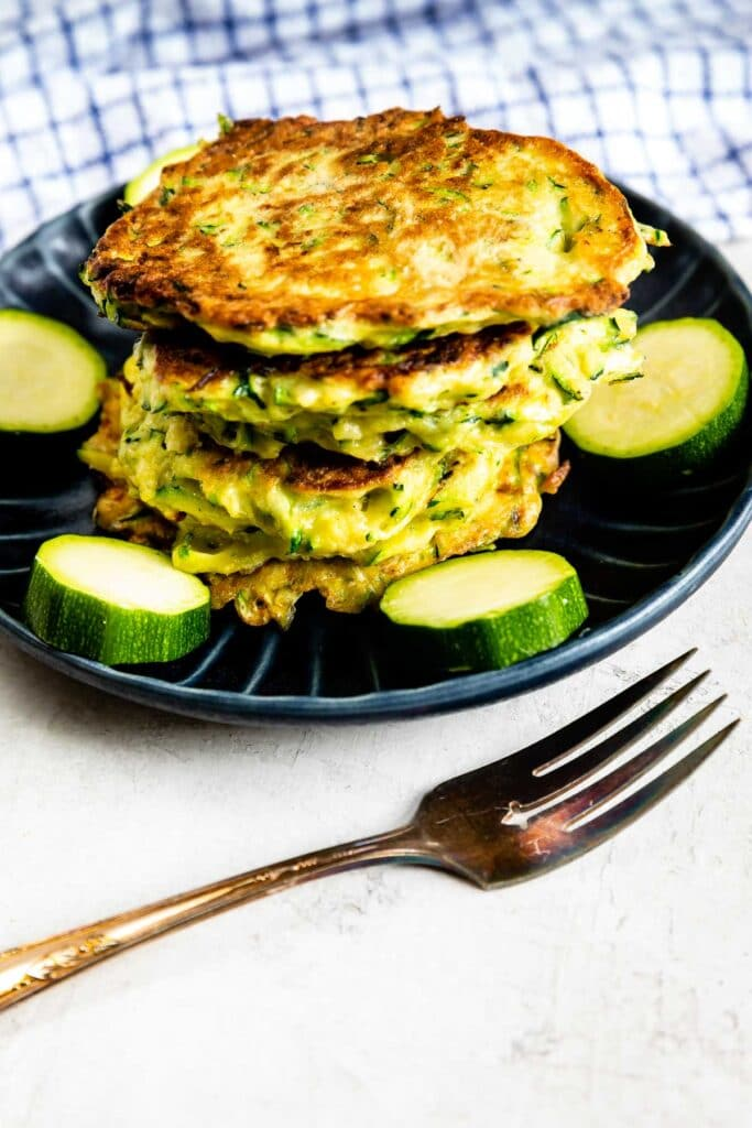 Stack of zucchini fritters on a plate surrounded by circled zucchinis