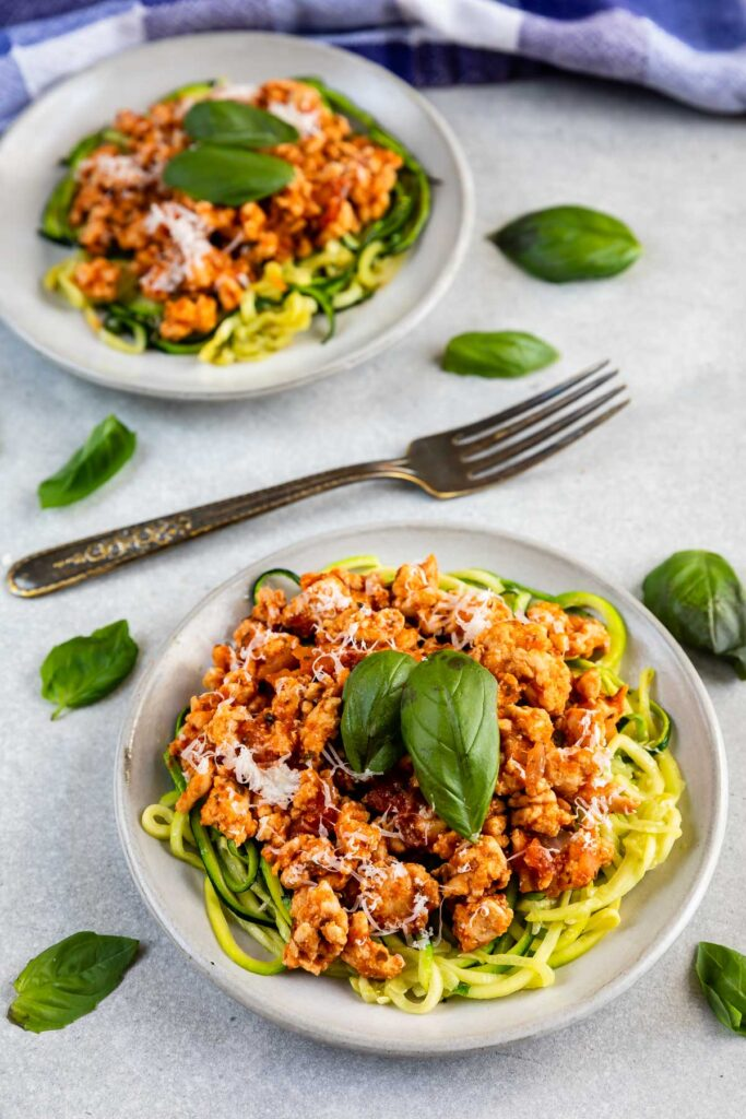 Two plates of zucchini noodles with meat sauce