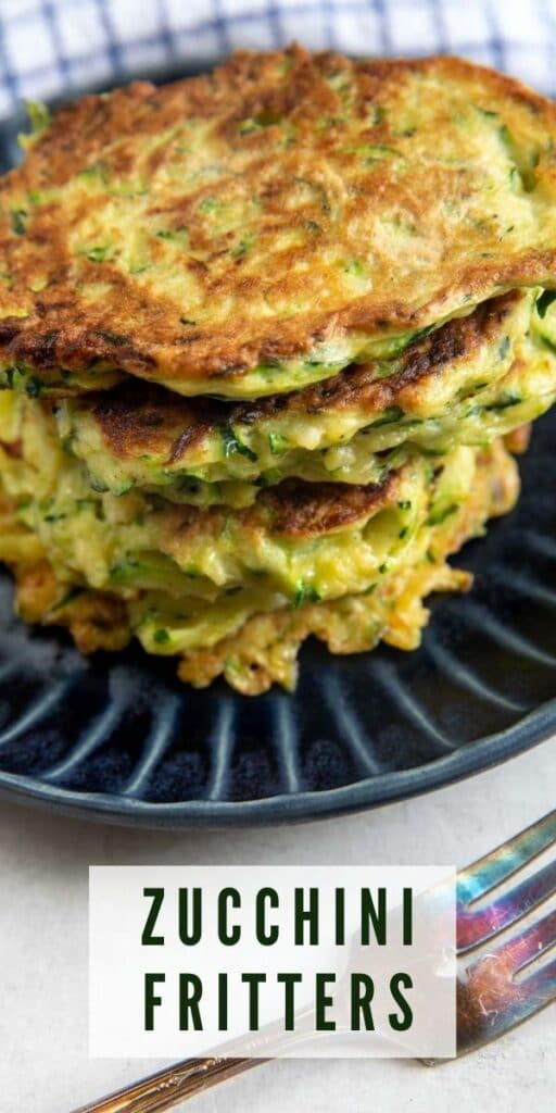 Stack of zucchini fritters on a blue plate with a fork next to it and recipe title on bottom of photo