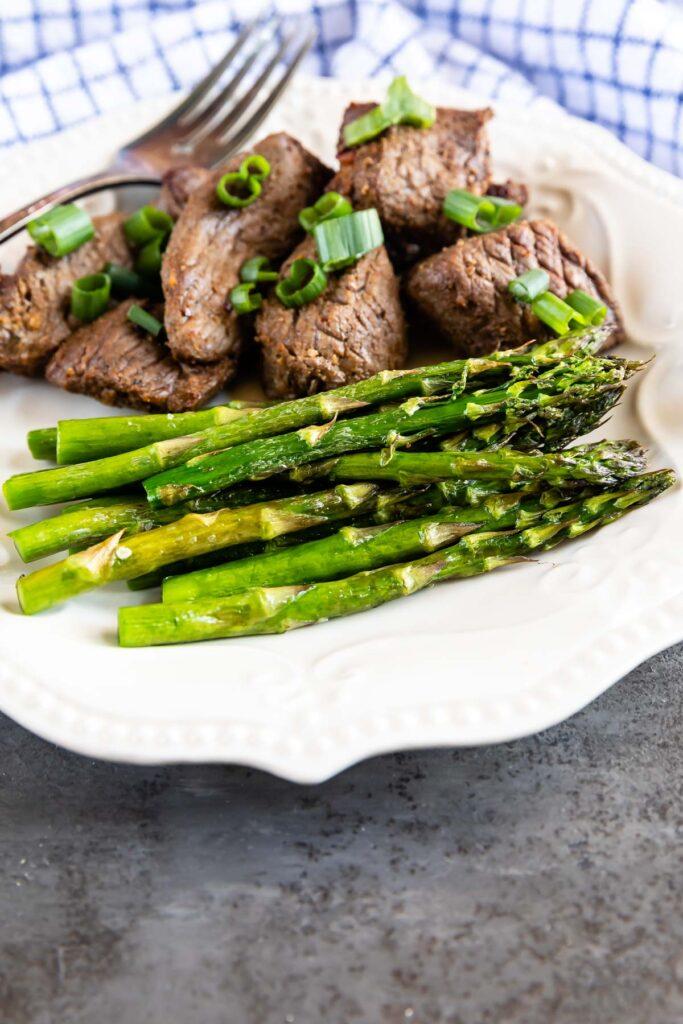 Air fryer asparagus plated next to steak