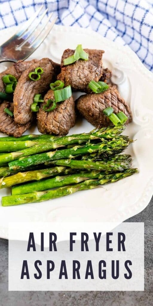 Air fryer asparagus plated next to steak with recipe title on bottom of photo