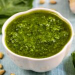 Basil pesto in a small white dish with garlic, toasted pine nuts and basil around it