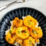 Overhead shot of curry shrimp served over rice on a plate