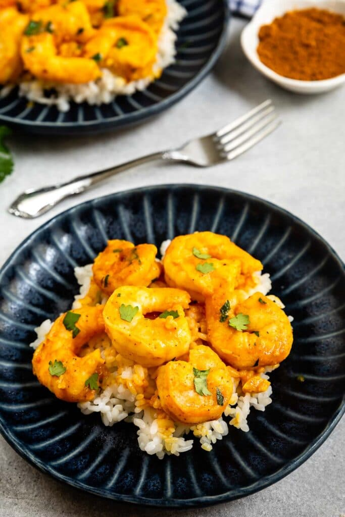 Two plates of curry shrimp served over rice