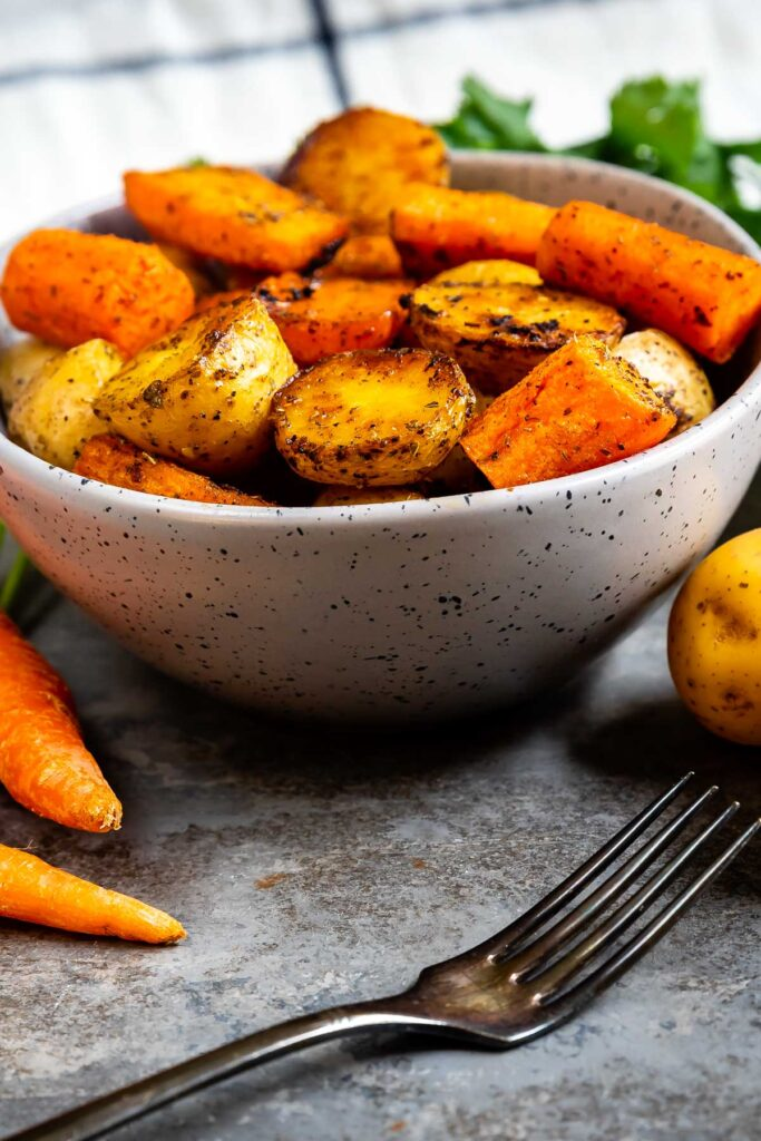 Bowl full of roasted potatoes and carrots with a fork in front of it