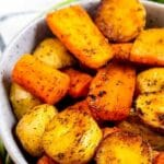 Close up shot of roasted potatoes and carrots with recipe title on top of image