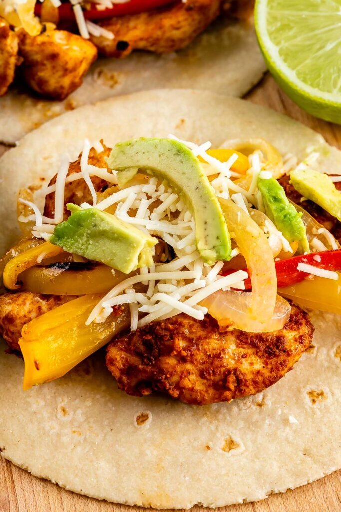 Close up of tortilla filled with sheet pan chicken fajitas, peppers, cheese and avocado