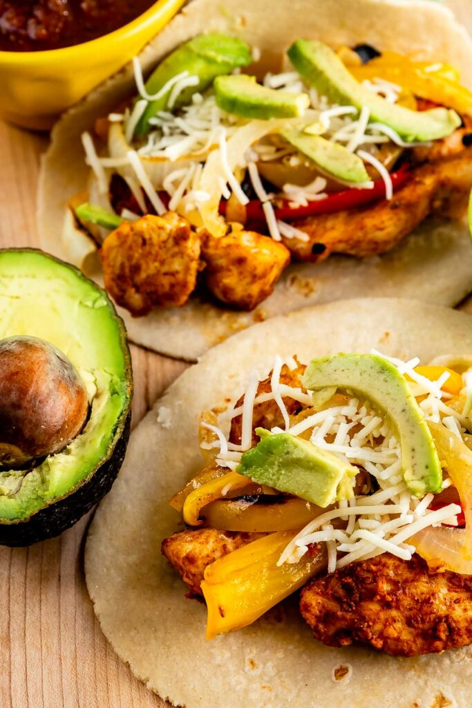 Two tortillas filled with sheet pan chicken fajitas, peppers, cheese and avocado