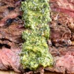 Close up of sliced skirt steak with chimichurri sauce and recipe title on bottom of photo
