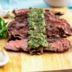 Sliced skirt steak on a cutting board with chimichurri sauce on top