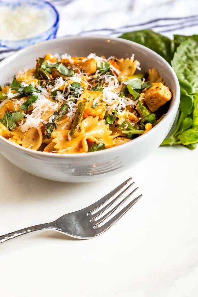 Bowl of sun-dried tomato pesto pasta with fork next to it