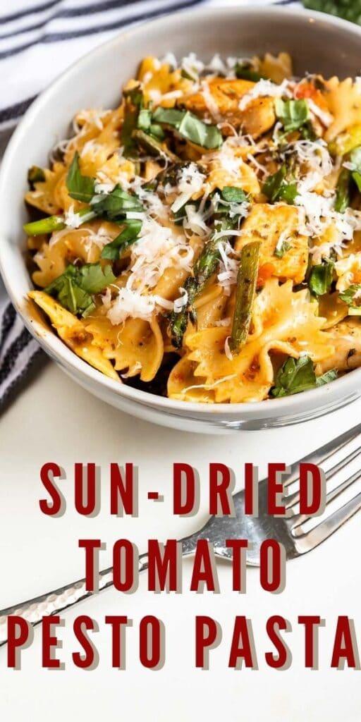 Overhead shot of sun-dried tomato pesto pasta with recipe title on bottom of photo