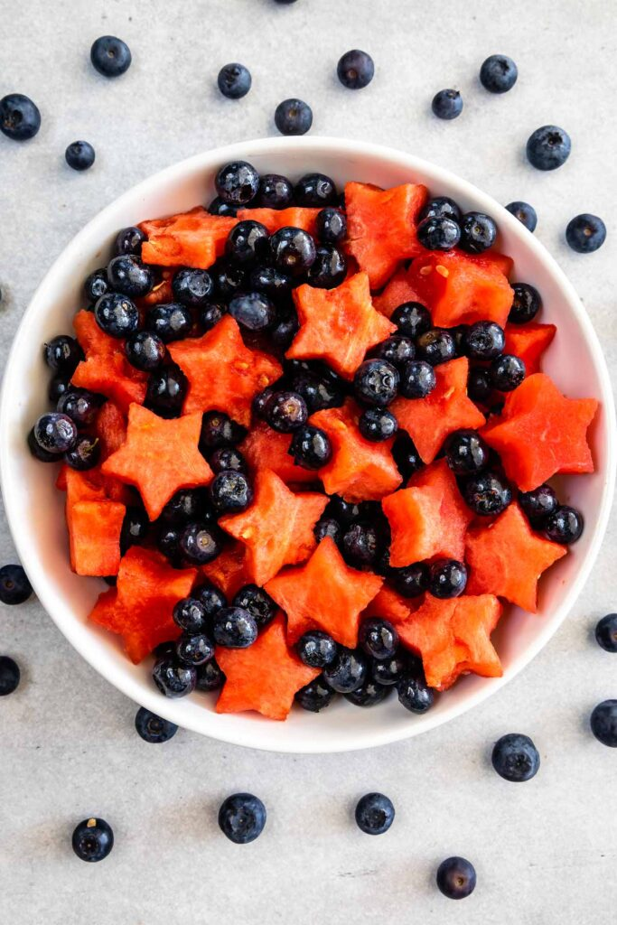 Overhead shot of big bowl of 4th of july fruit salad with blueberries all around the bowl