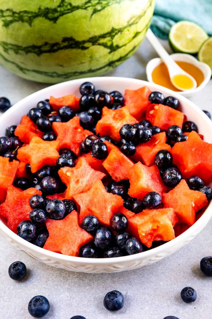 Big bowl of fruit salad with watermelon and dressing in background