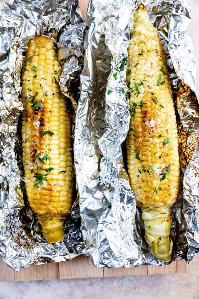 Overhead view of garlic butter grilled corn on the cob unwrapped from foil