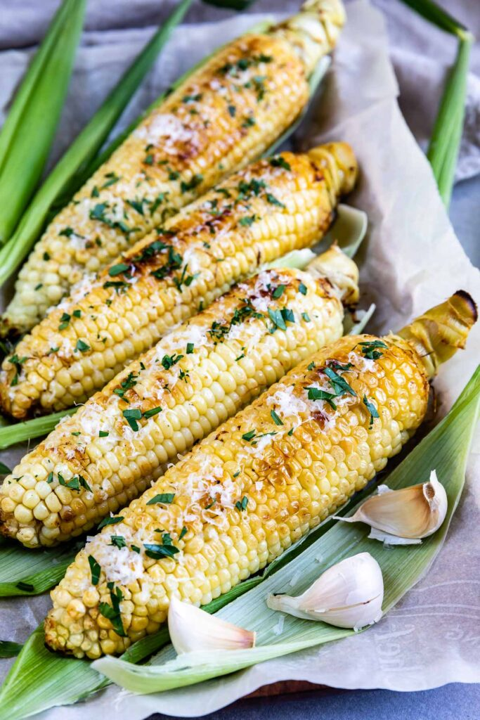 Four ears of garlic butter grilled corn on the cob