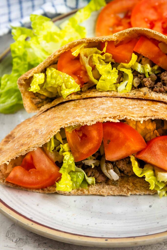 Close up shot of two ground beef gyros loaded with traditional gyro toppings