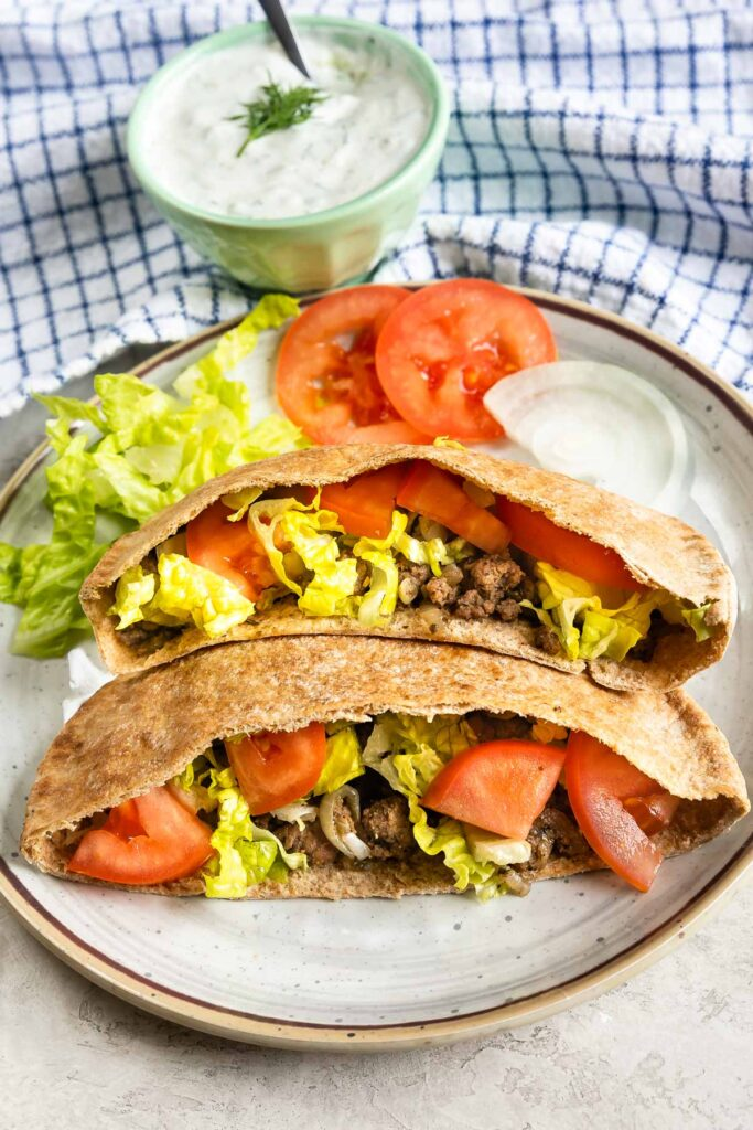 Two ground beef gyros loaded with traditional gyro toppings