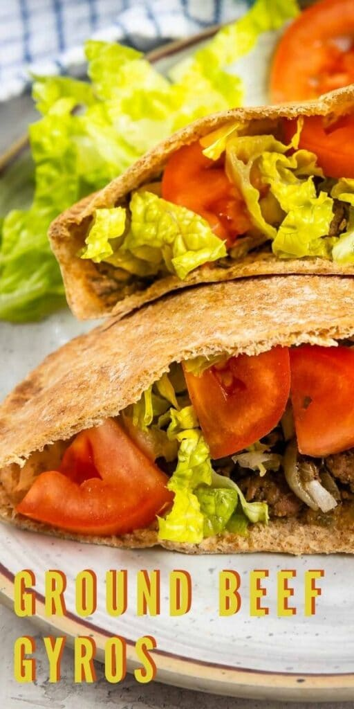 Close up shot of two ground beef gyros loaded with traditional gyro toppings and recipe title on bottom of image