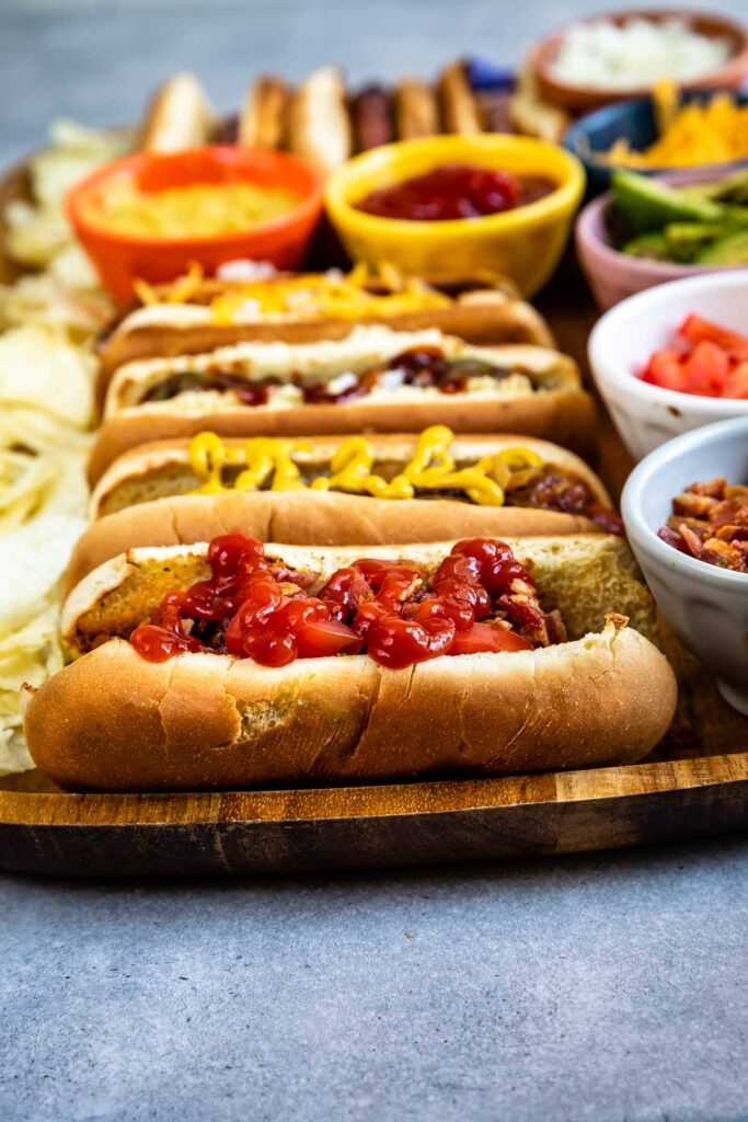 Side shot of hot dog bar showing different hot dogs and toppings