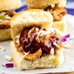 Three instant pot pulled pork sliders on parchment paper