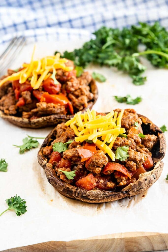 Two taco stuffed portobello mushrooms topped with shredded cheese