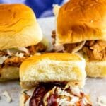 Three instant pot pulled pork sliders on parchment paper and recipe title on top of image