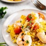 Two plates of shrimp scampi with recipe title on bottom of photo