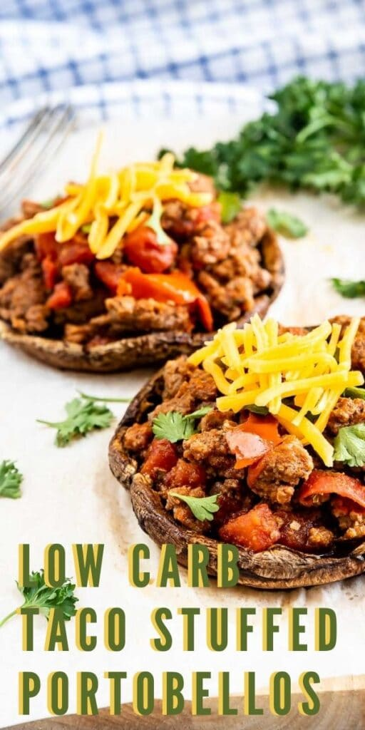 Two taco stuffed portobello mushrooms topped with shredded cheese and recipe title on bottom of image