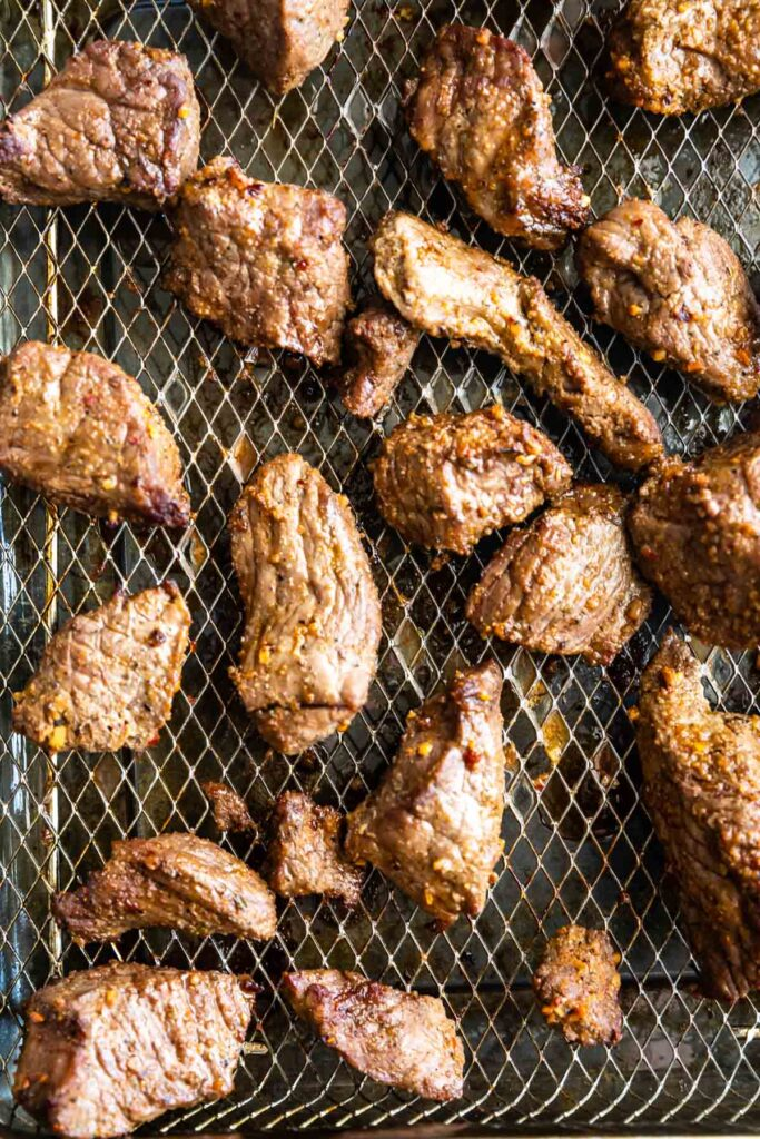Overhead shot of steak tips on air fryer rack