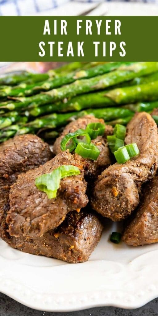 Plate full of air fryer steak tips with asparagus and recipe title on top of image