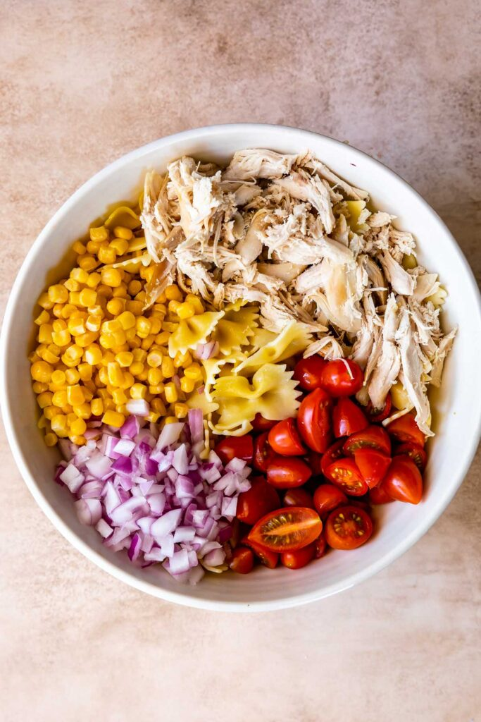 Overhead shot of BBQ chicken pasta salad in a bowl before being mixed