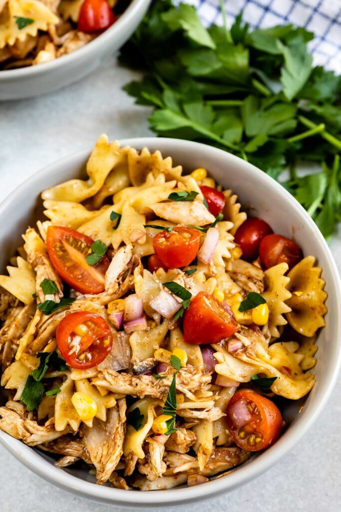 Overhead shot of BBQ chicken pasta salad in bowl with herbs behind it