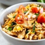 Two bowls full of BBQ chicken pasta salad with recipe title on bottom of photo