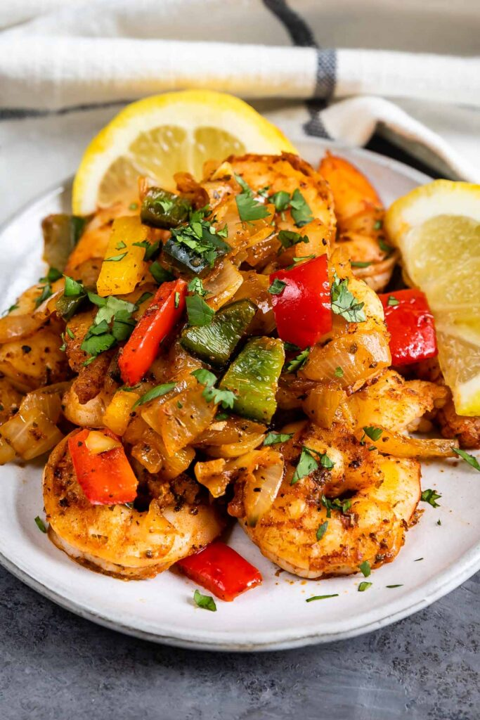 Plate full of cajun shrimp with bell peppers and fresh lemon slices